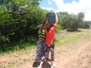 Experiencing the burden of 20litres of water traditionally carried by women on their head from the river to their village in Siamtelele, Zimbabwe
